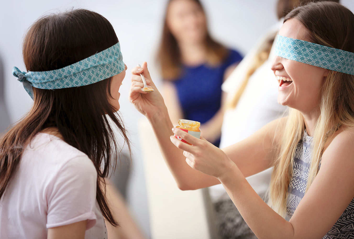 women taste testing baby food at a baby shower.