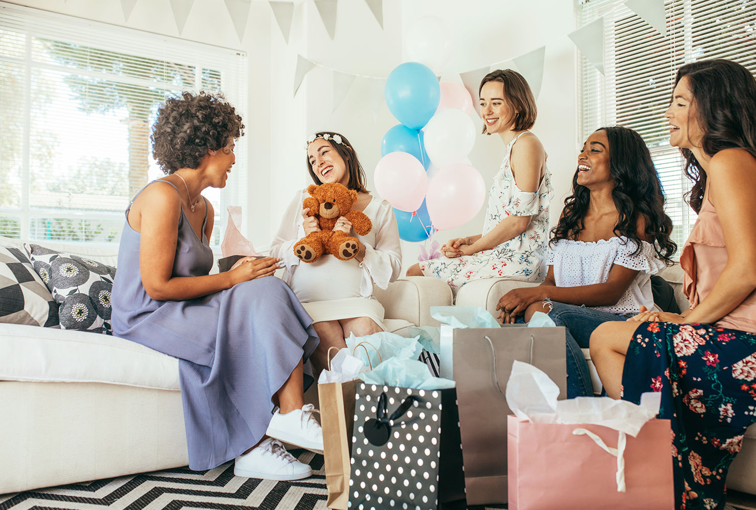 Pregnant mom surrounded by her friends at her baby shower.